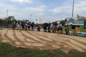 A large group shovels the first dirt at the event.