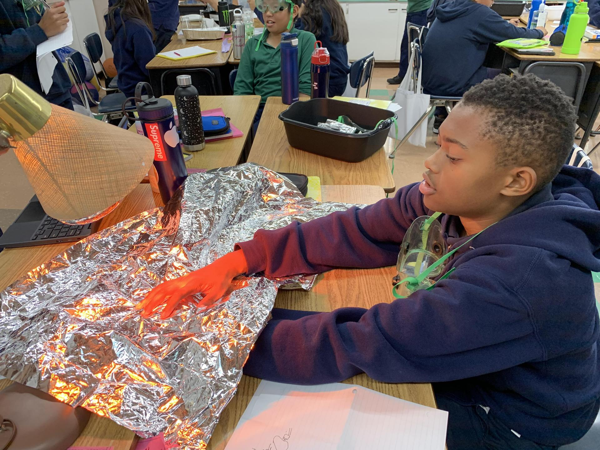 Students examining properties of insulation during thermal energy transfer.