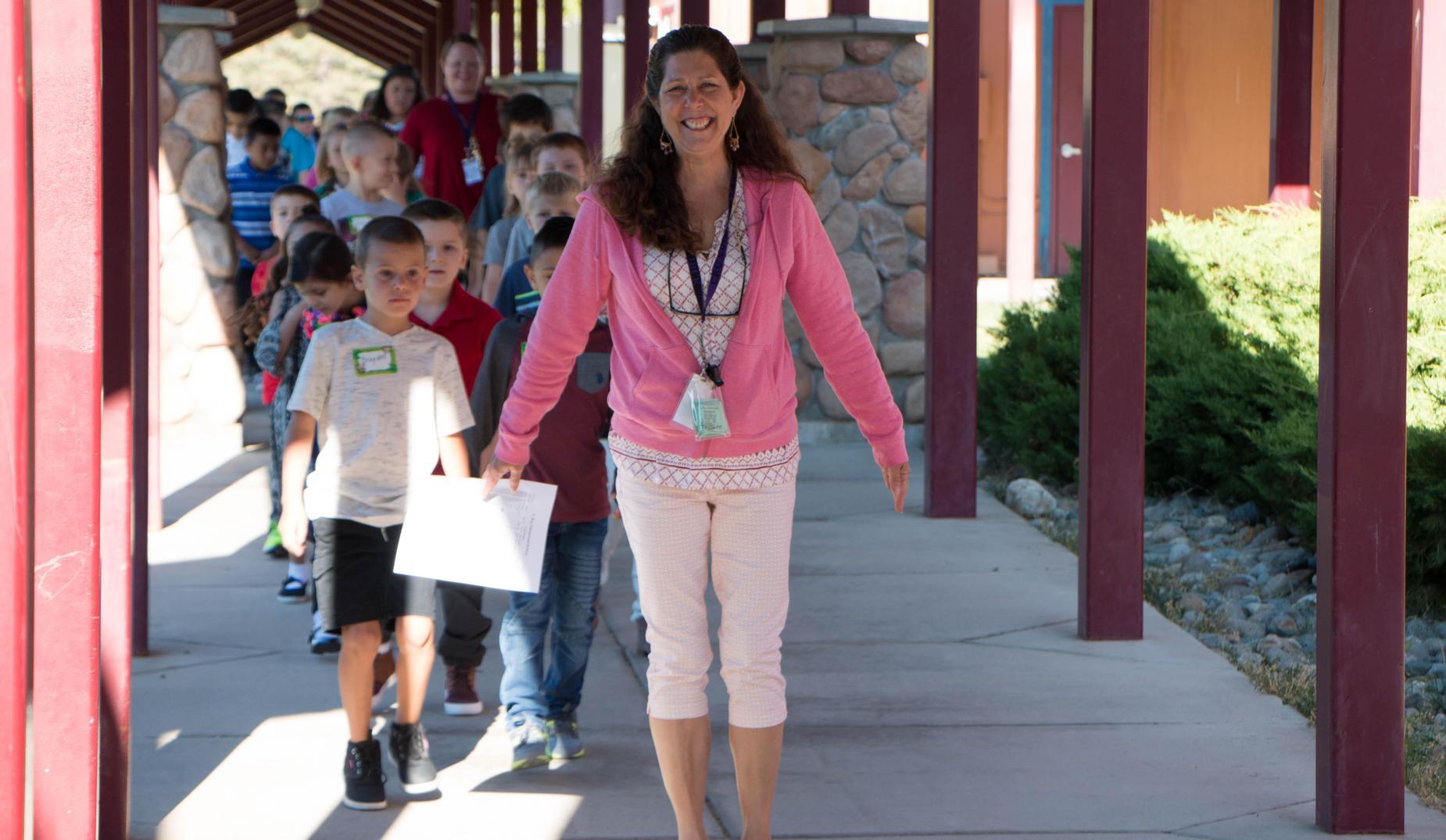 Teacher leading students down the hallway