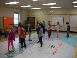 Students walking on and learning about the giant NC map.