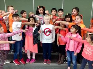 Students at Moxee Elementary wearing orange and pointing to a boy wearing a shirt that says no bullying.