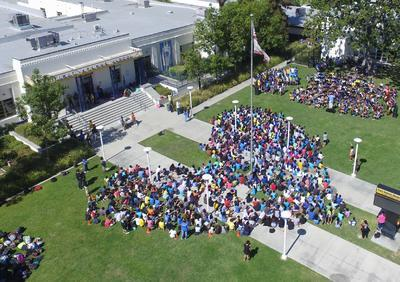 students in a heart shape on the front lawn