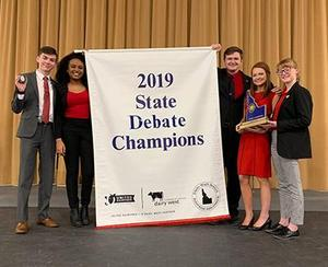 The five debate team members pose with their State Debate Champions banner.