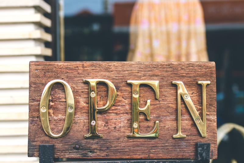 Open in gold letters on wood.