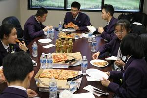Students at table eating pizza
