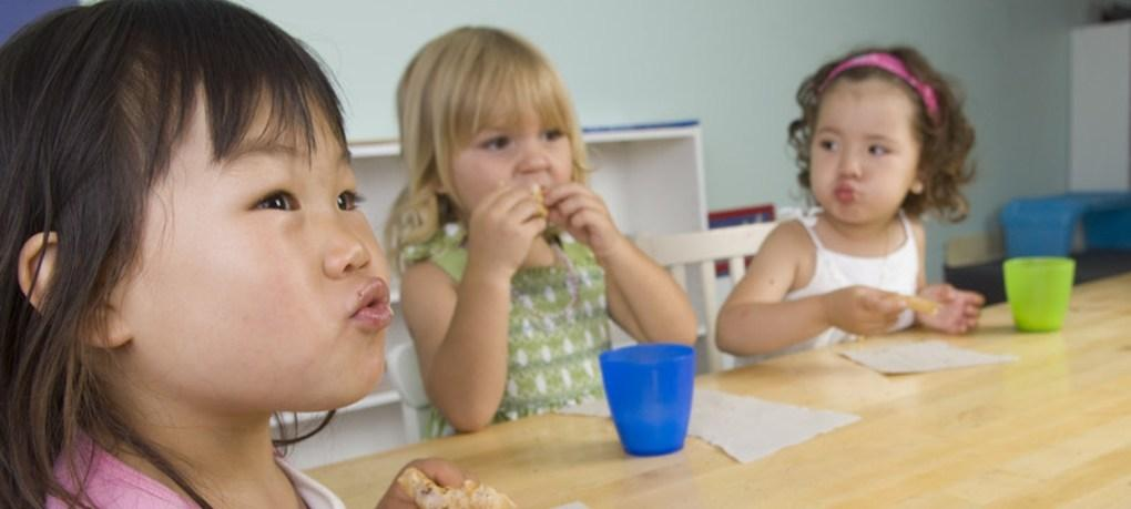 Three preschoolers eating snack at a table.