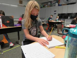 A student works on writing her letter to her pen pal.