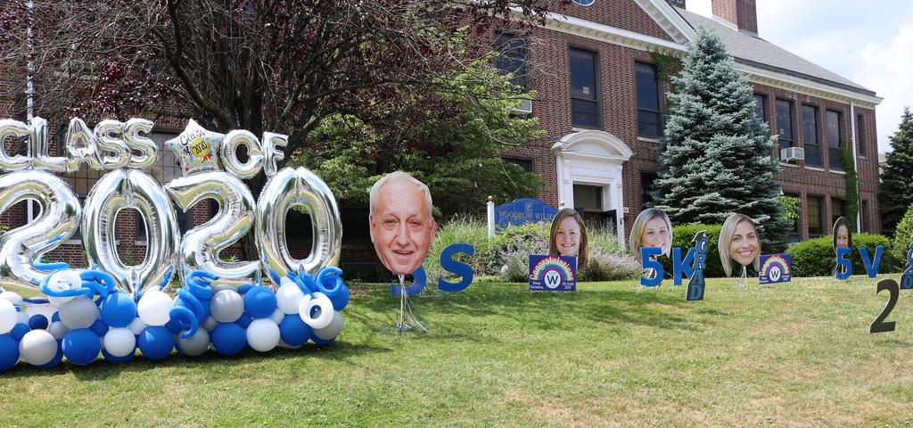 """Photo of Class of 2020 balloons and principal/staff """"fat heads"""" on school lawn."""