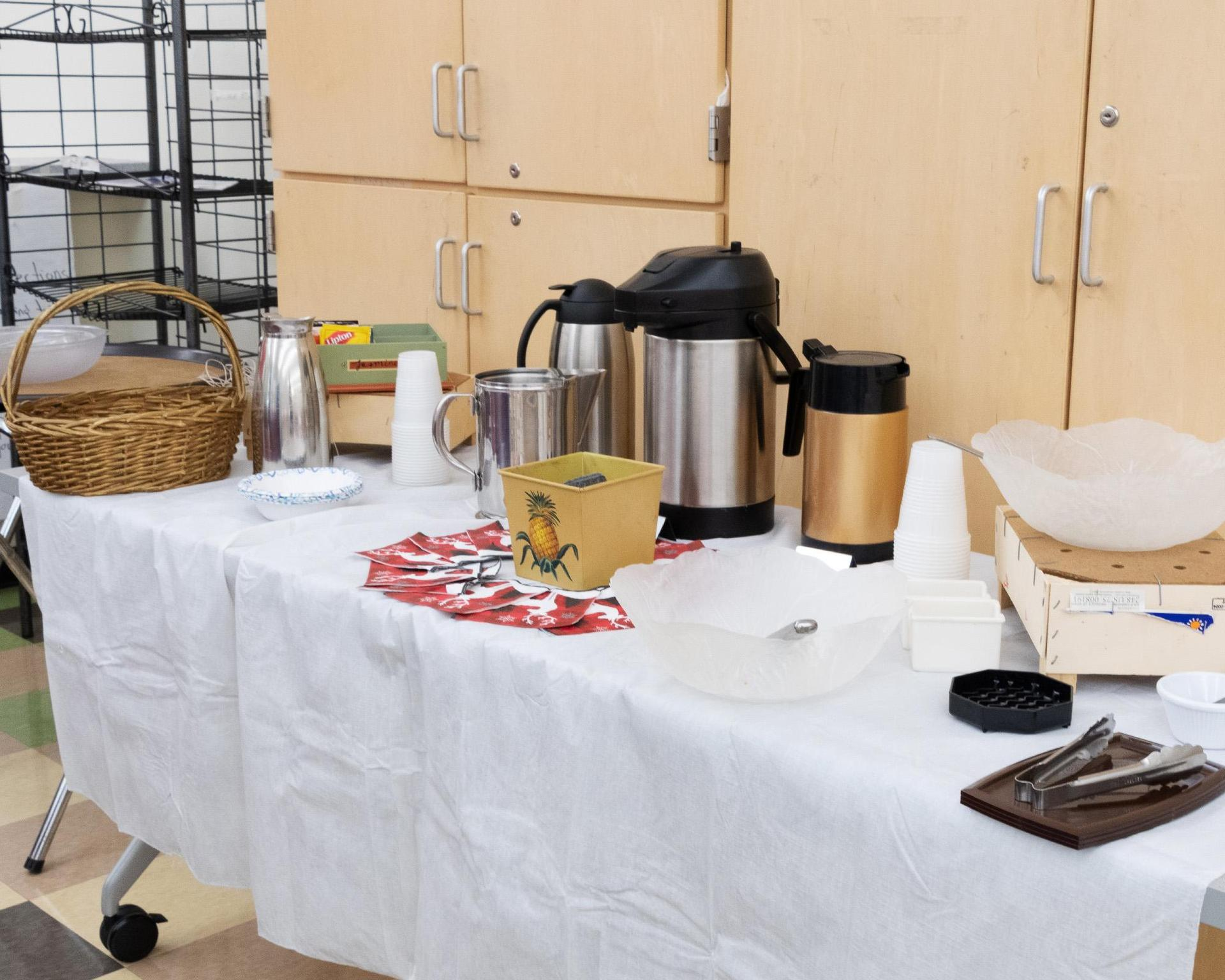 A table with a pot of coffee and accessories