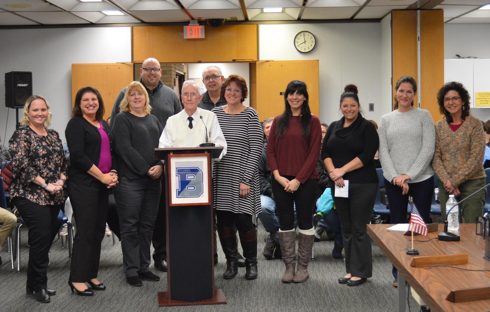 8 female teachers standing around the podium with JFTK president, Mr. Ralph Douglass and treasurer, Mr. Jim Gilbert