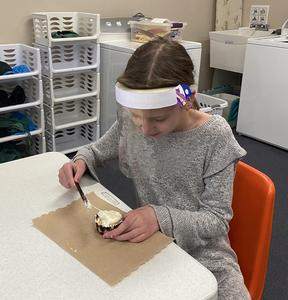 student frosting cupcake