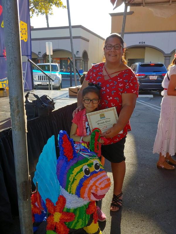 parent and student standing next to award winning piñata