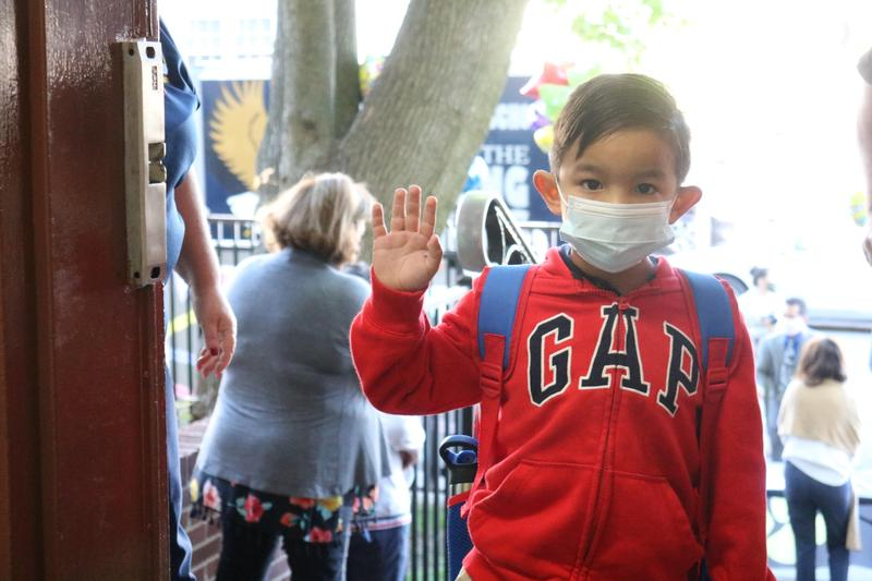 Boy wearing mask and red jacket waving