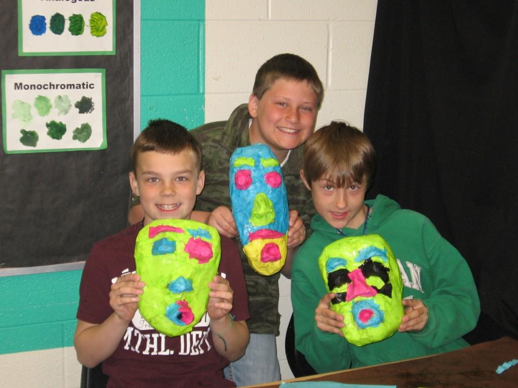 three boys show off the masks they made