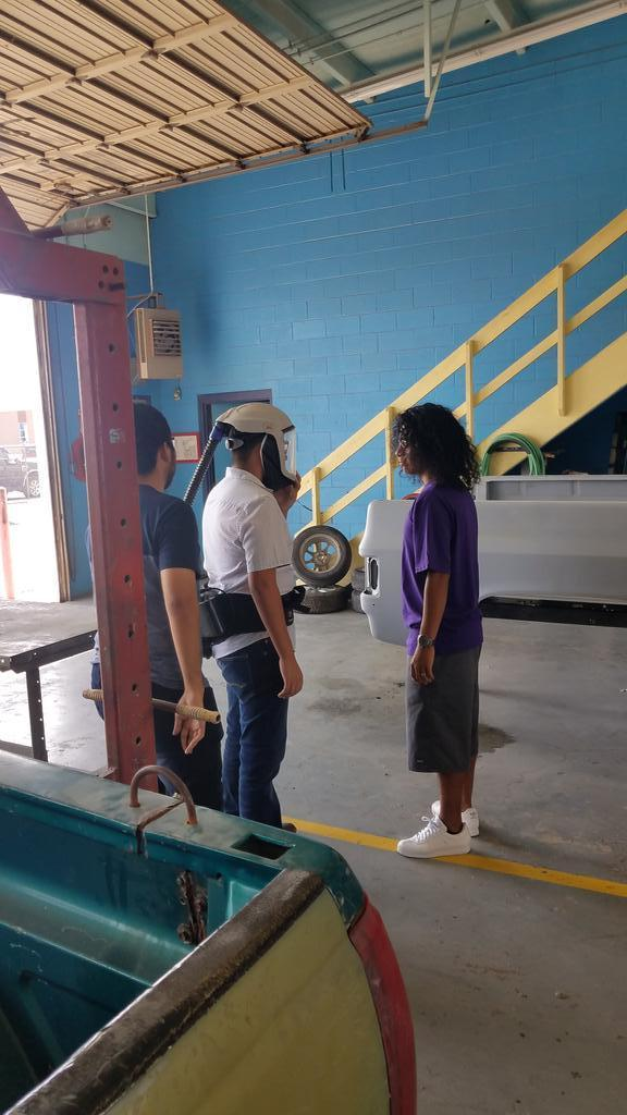 student with helmet and connected hose standing with two students