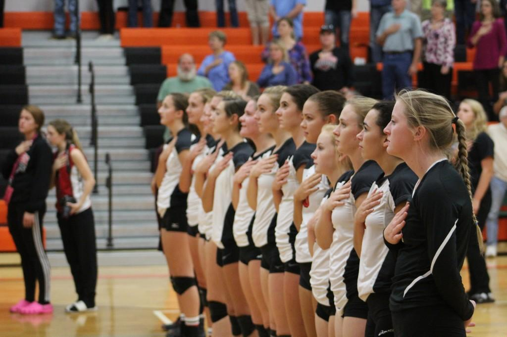 Ladies volleyball team standing in a line during the National Anthem