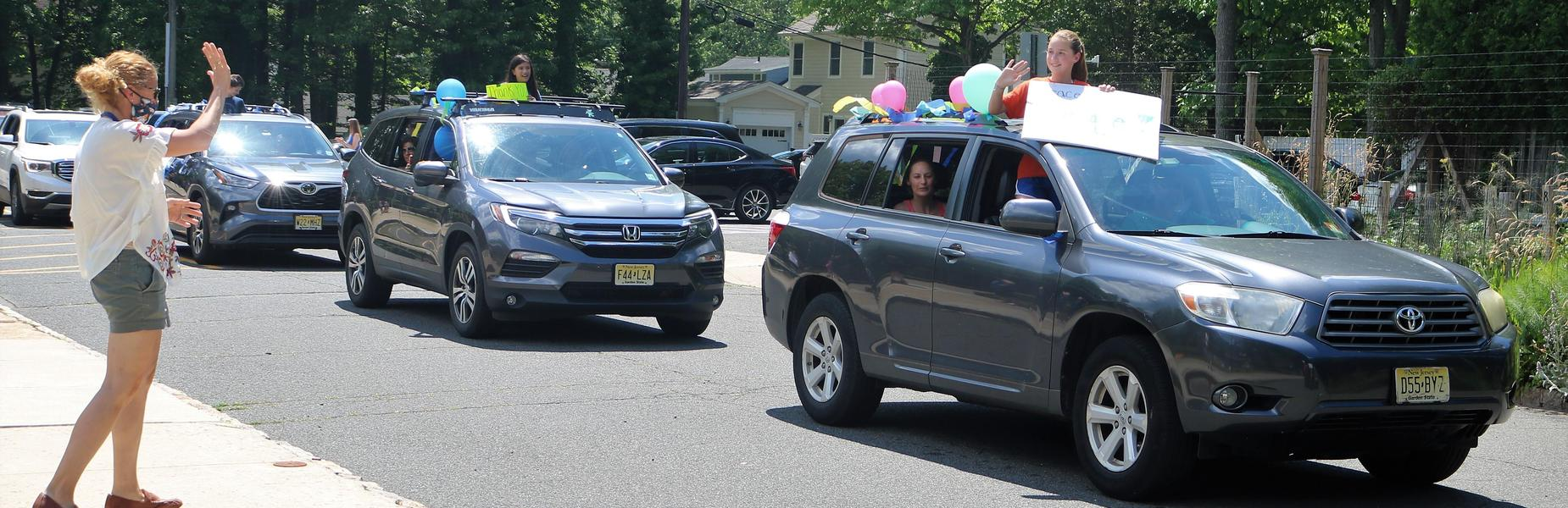 Photo of Tamaques teacher waving to student during drive thru Grade 5 Clap Out