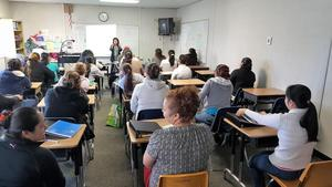 Parents attending a meeting in a classroom.