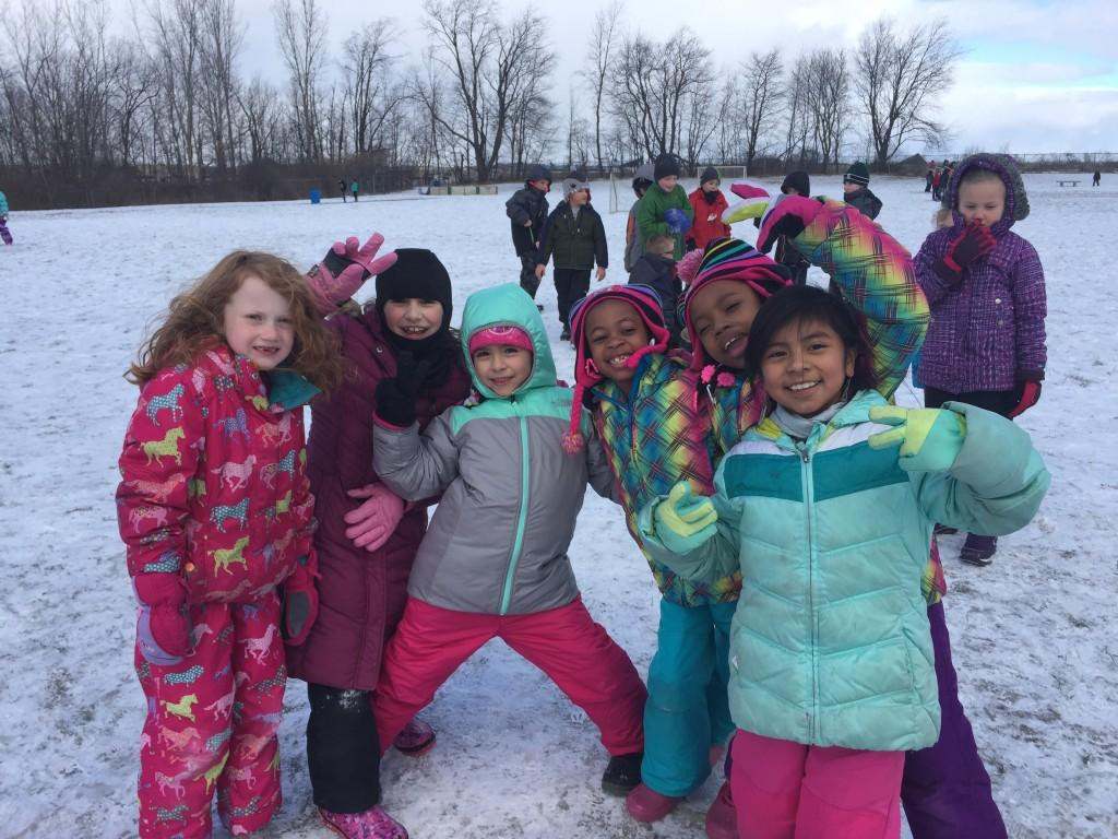 six girls in snowsuits pose for camera