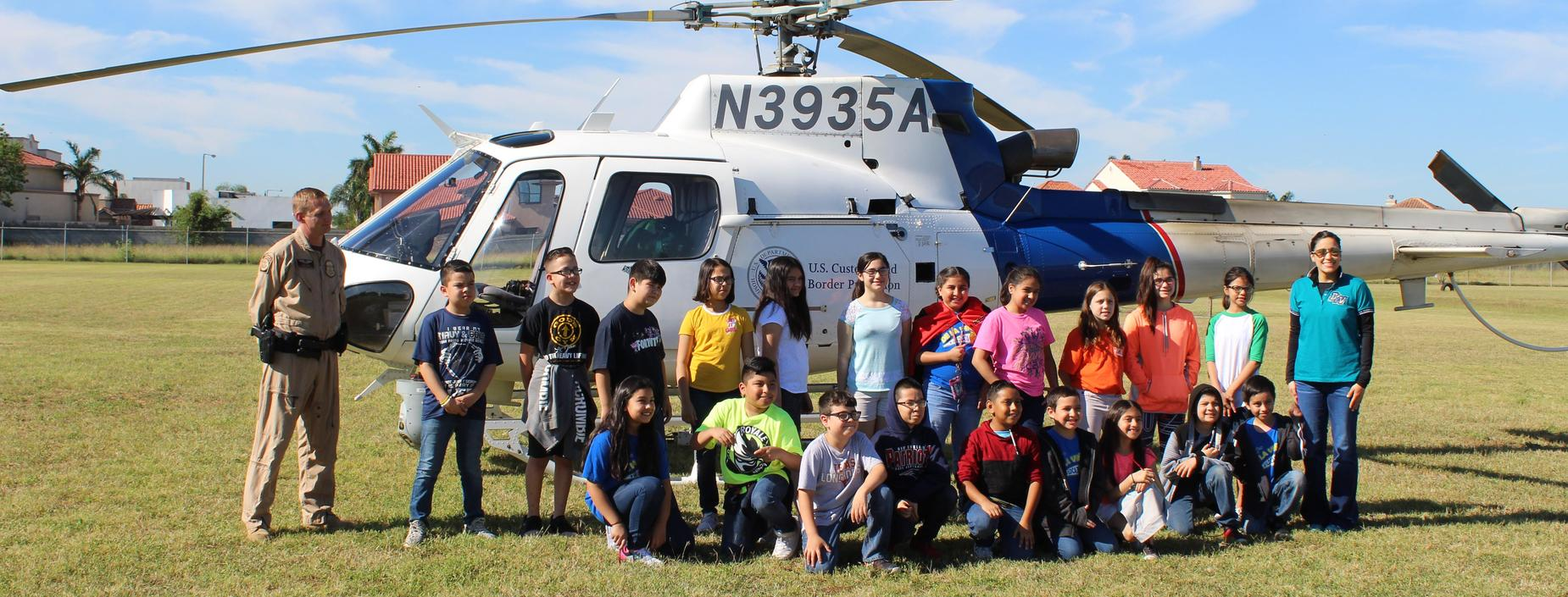 Ms. Caceres' 4th grade class posing with Customs helicopter on Career Day