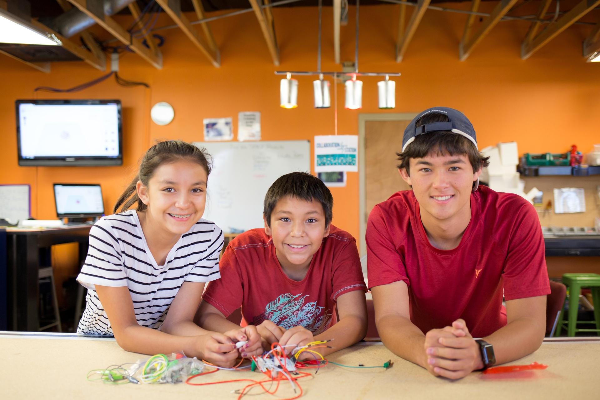 Three students smile at camera in the makerspace