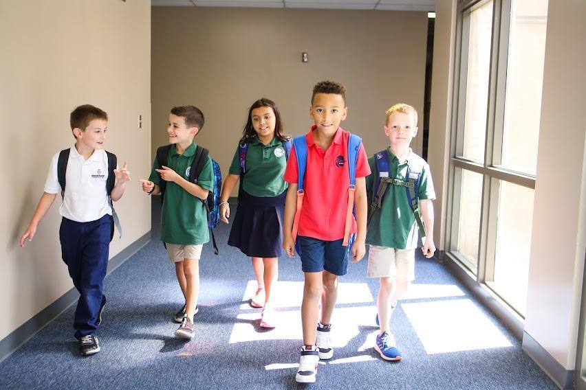 Children with backpacks in school building