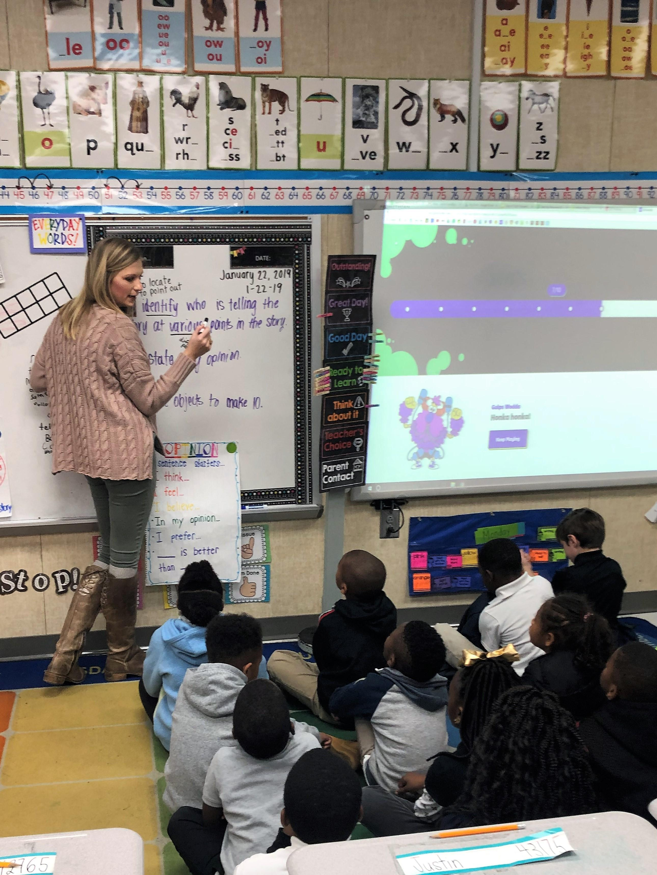 Teacher instructing students with anchor chart