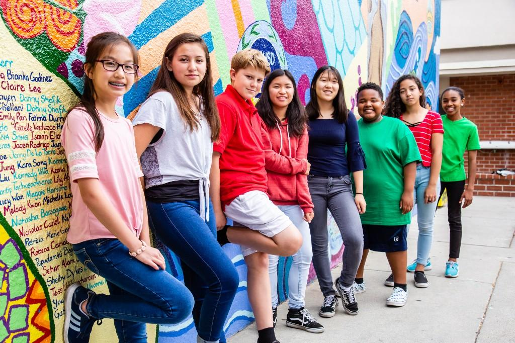 Students standing in front of mural