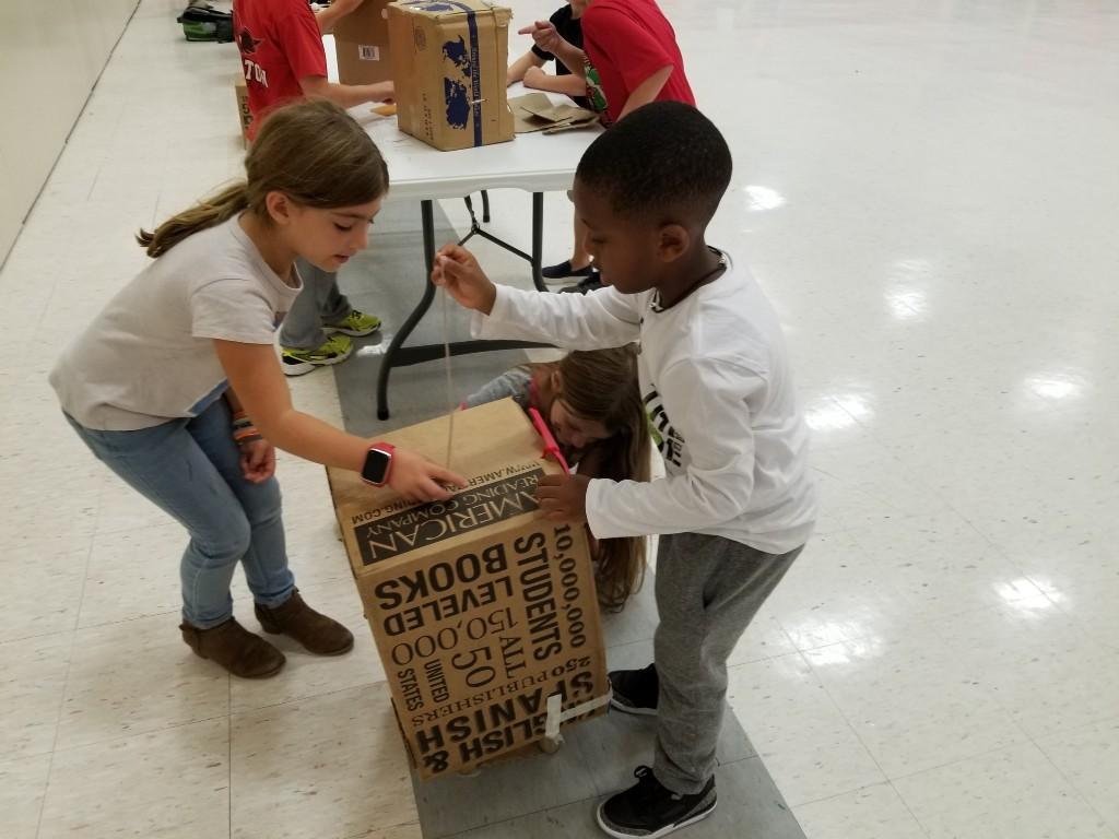 Student playing cardboard arcade game.