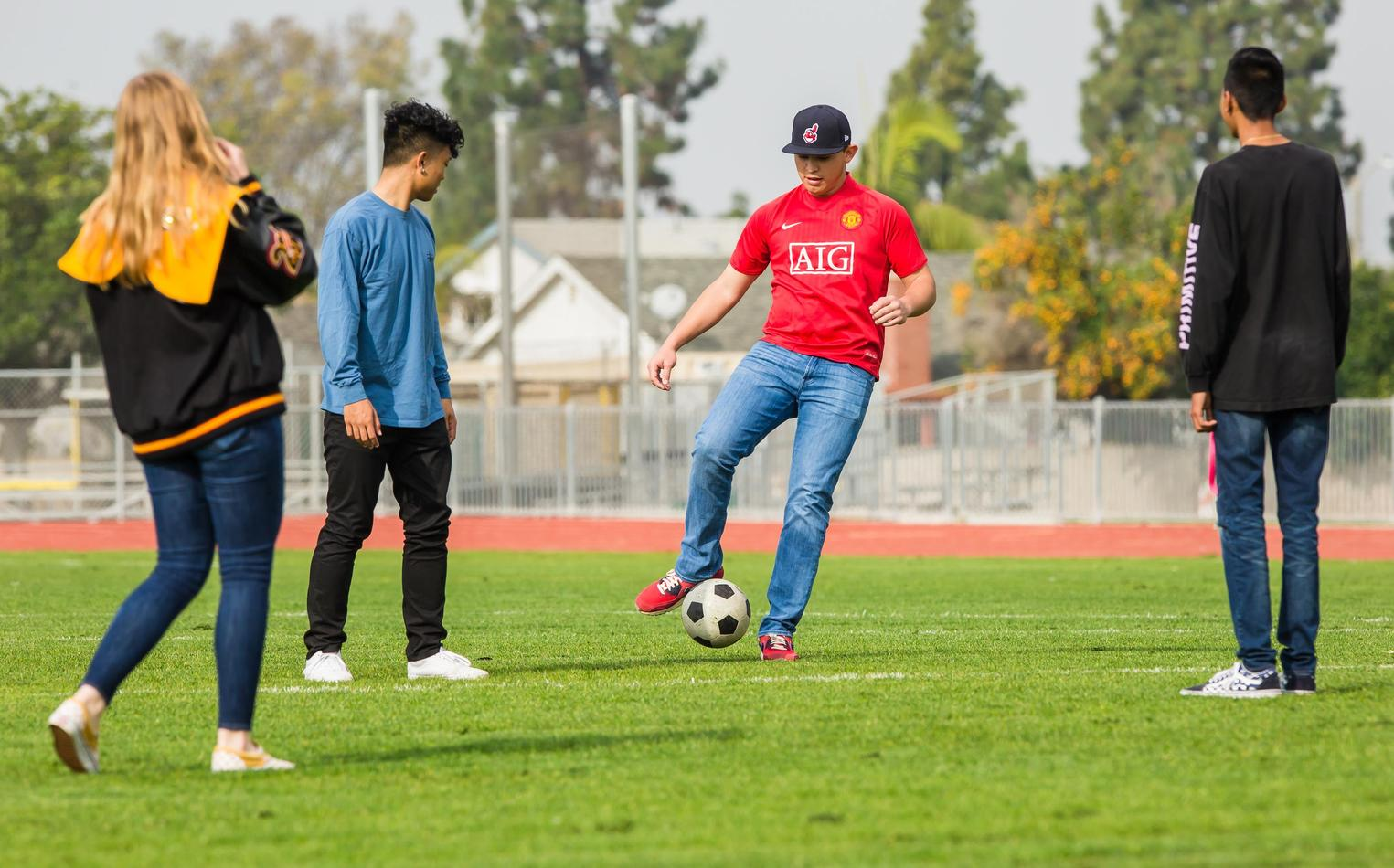 Four high school students kicking a soccer ball after class.