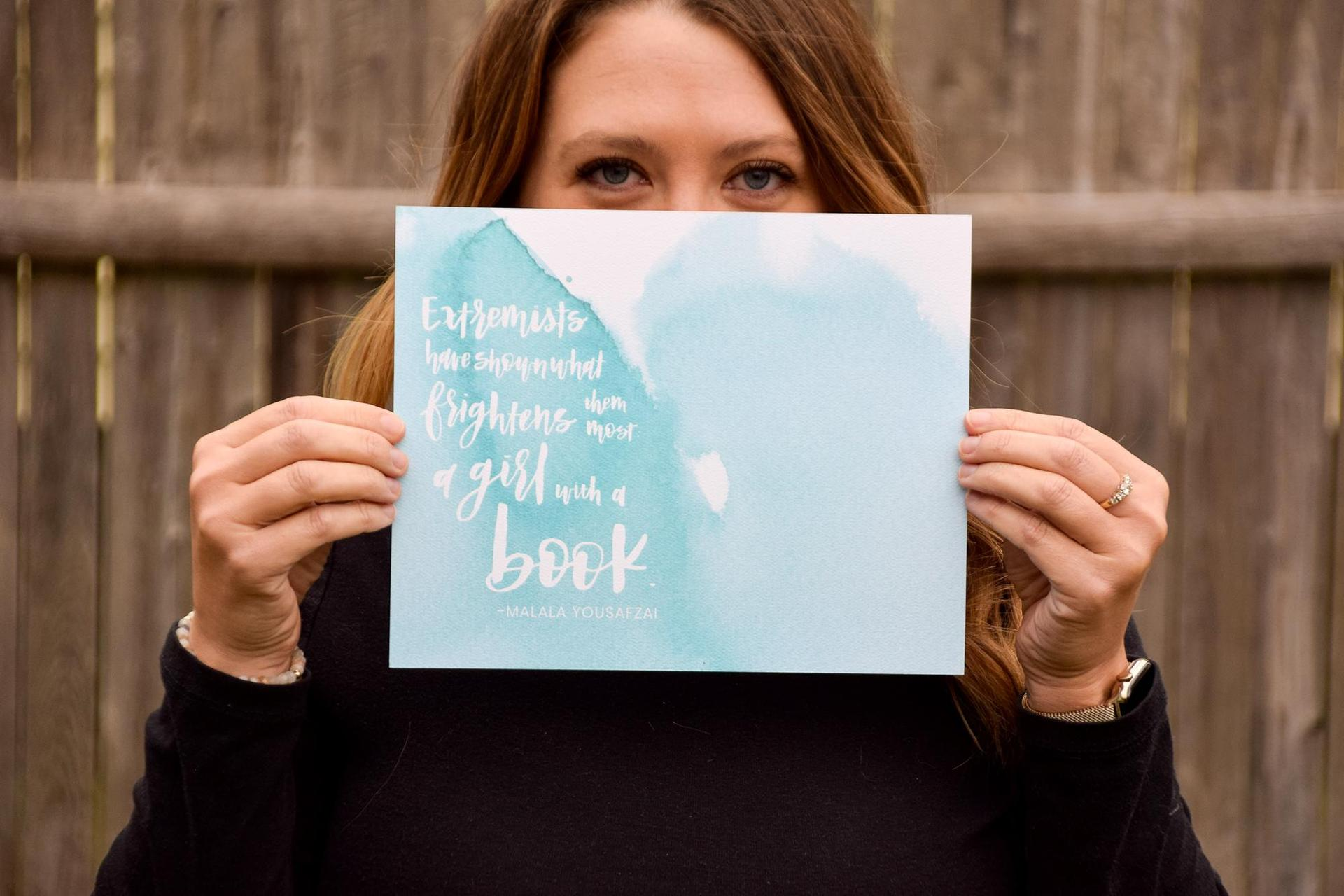 Woman holding up a card with an inspirational quote, face partially hidden