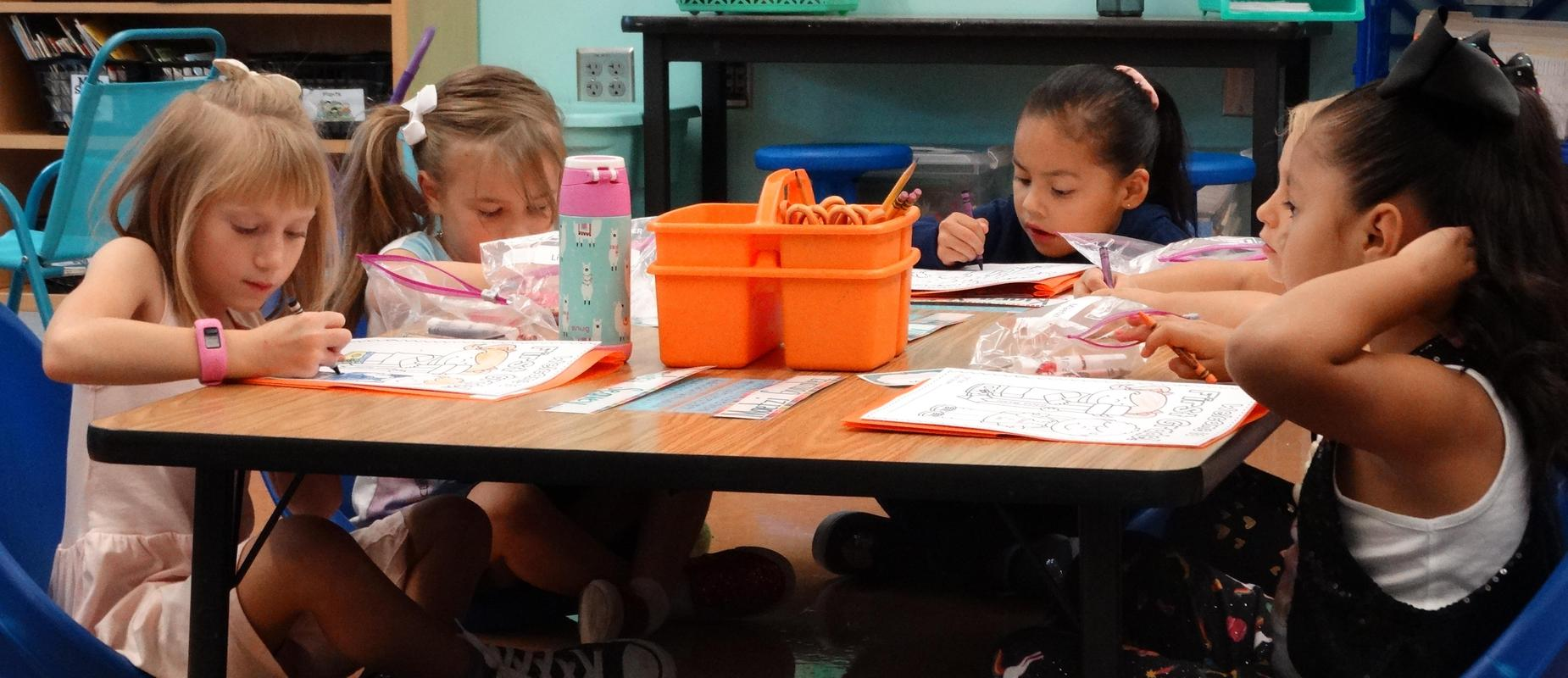 Five female students working on coloring pages at their table while seated on the ground