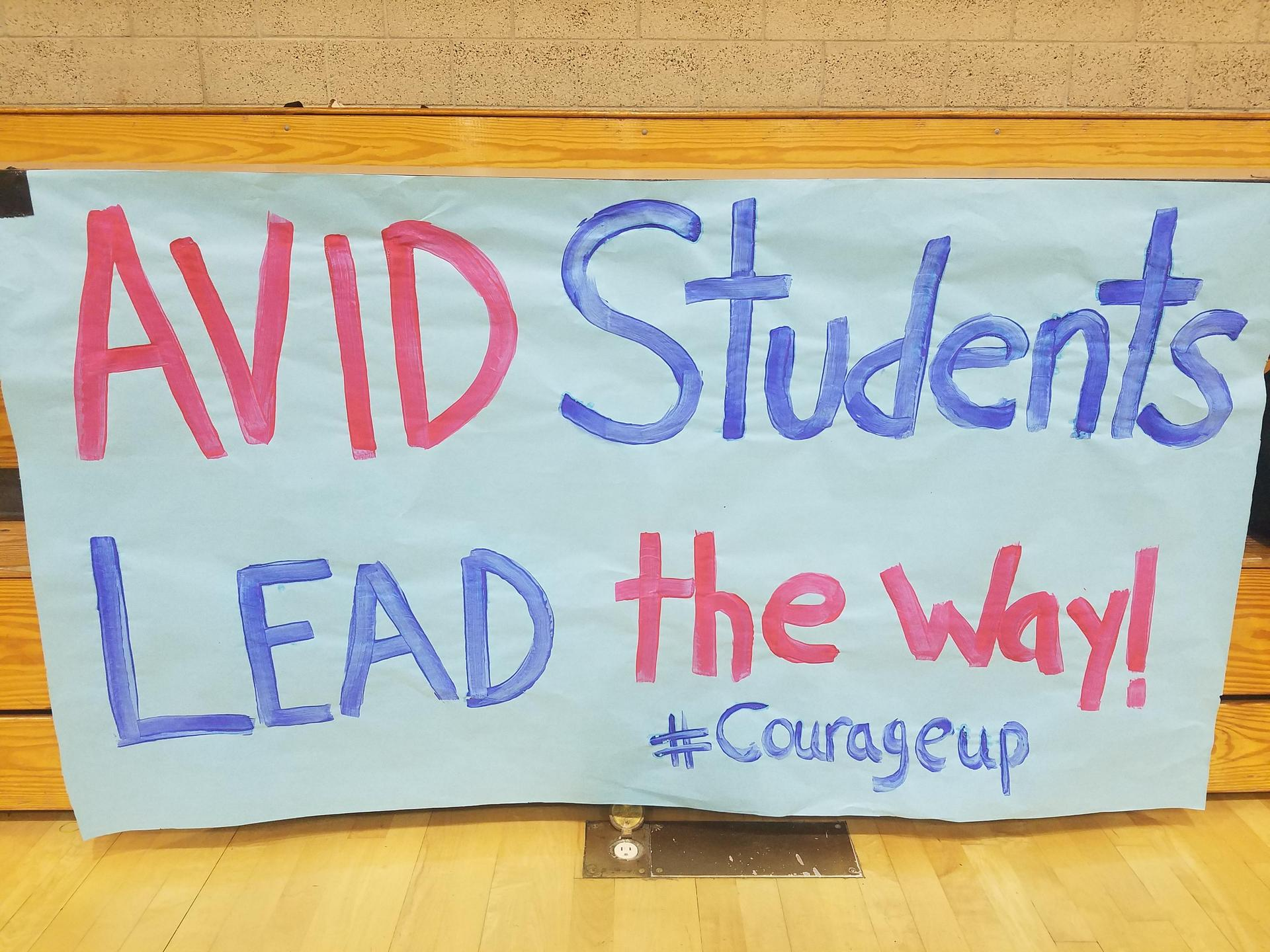 Closeup of a poster with the caption 'AVID Students Lead The Way!' and hashtag  courage up.