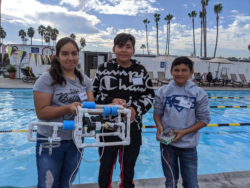 Picture of kids holding the ROV by the pool