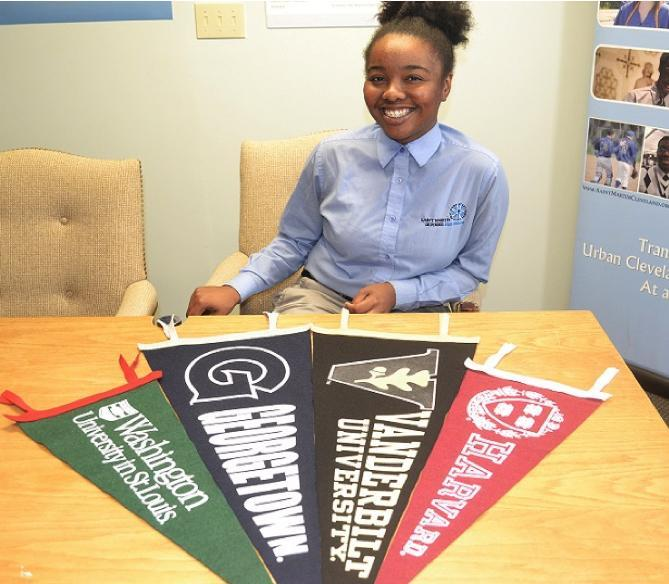 Girl sitting with college banners at table