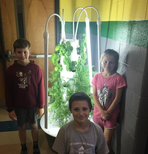 One of the Aeroponic towers and their caretakers.