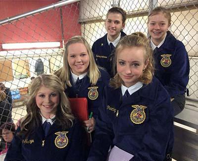 Five FFA members pose in the bleachers wearing their FFA jackets.