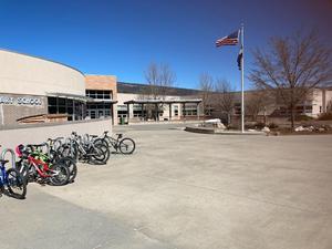 view of flag, bikes, at front door of school