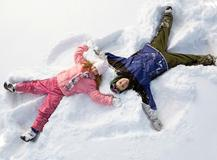 boy and girl laying in snow and making snow angels