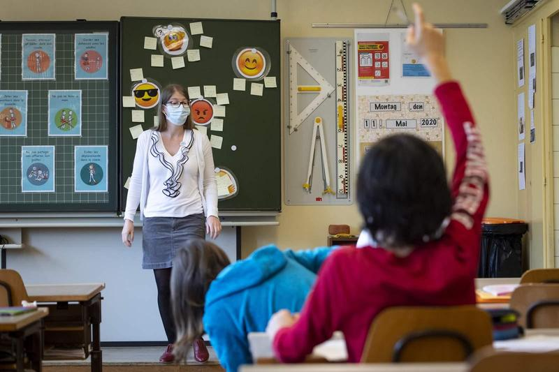 Teacher wearing face mask in front of classroom