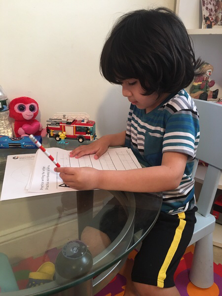 little boy at his table doing his work