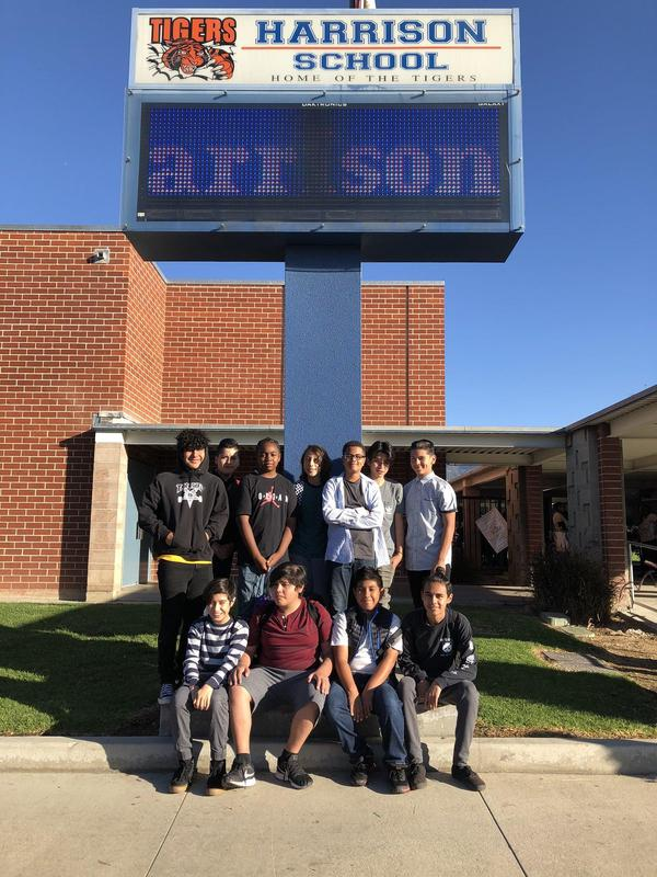 students pose in front of school sign