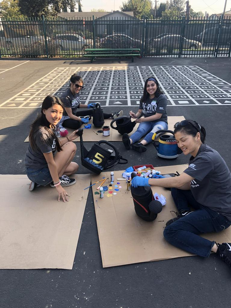 group of church members paint flower cans on blacktop
