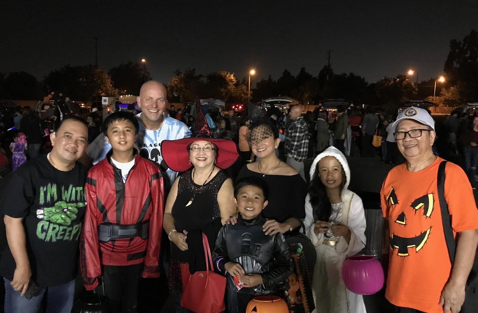 Family and principal in costumes at Trunk or Treat