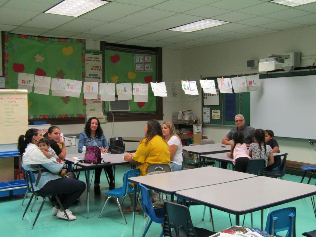 parents chatting while seated in a classroom
