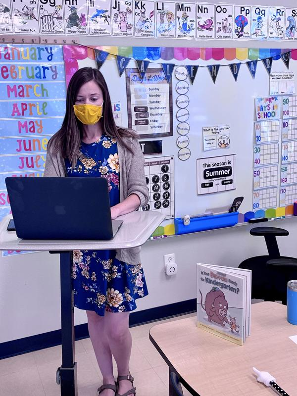 A teacher wearing a mask teaches remotely on her computer.