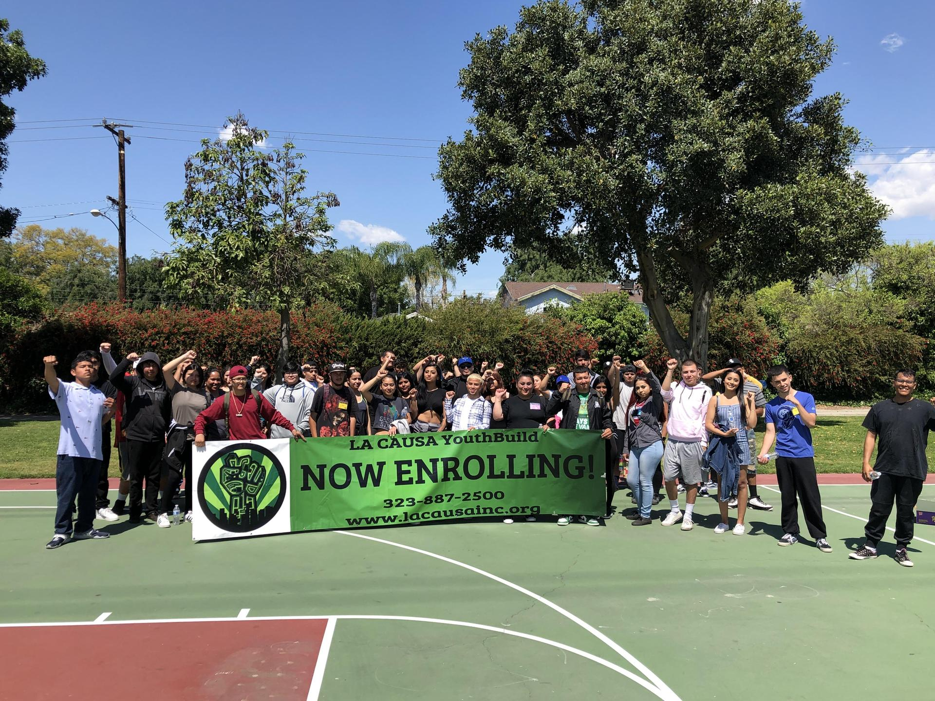 LA CAUSA Students pose with an enrollment banner during Mental Toughness