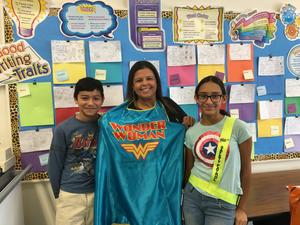 teacher wearing a wonder woman cape with a male and female student