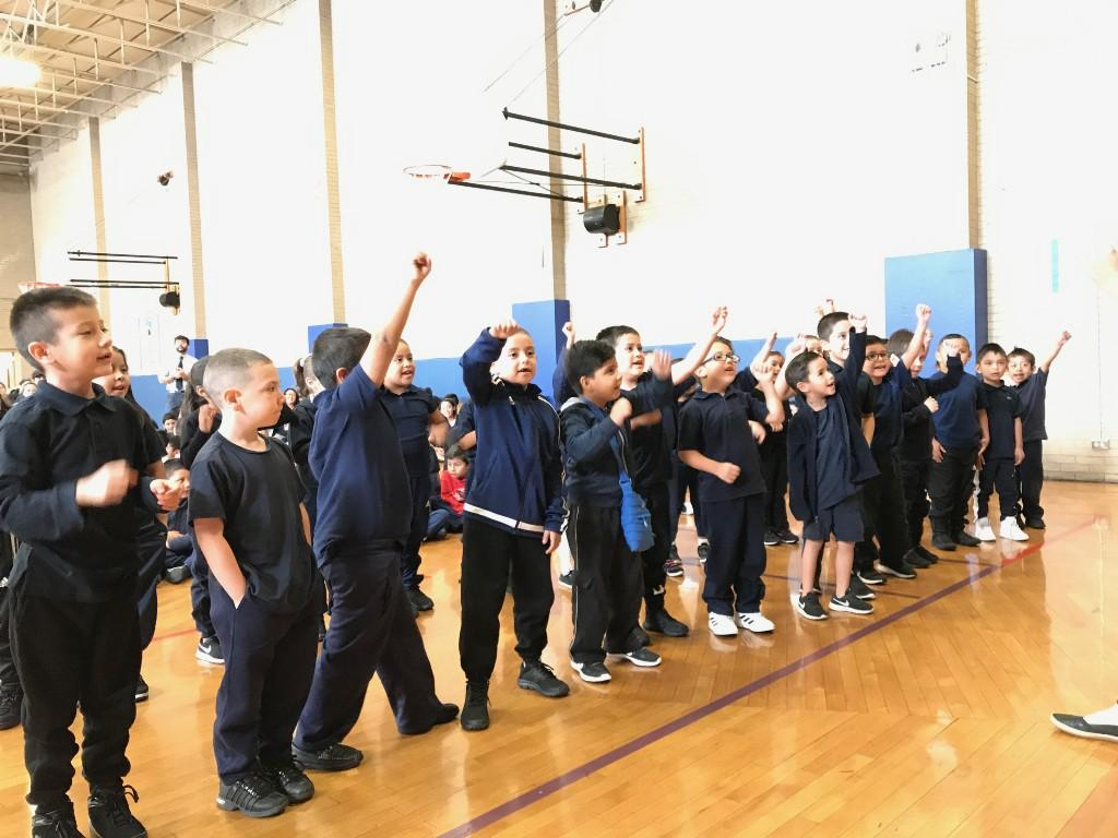 Kinder students raise their fists in a cheer