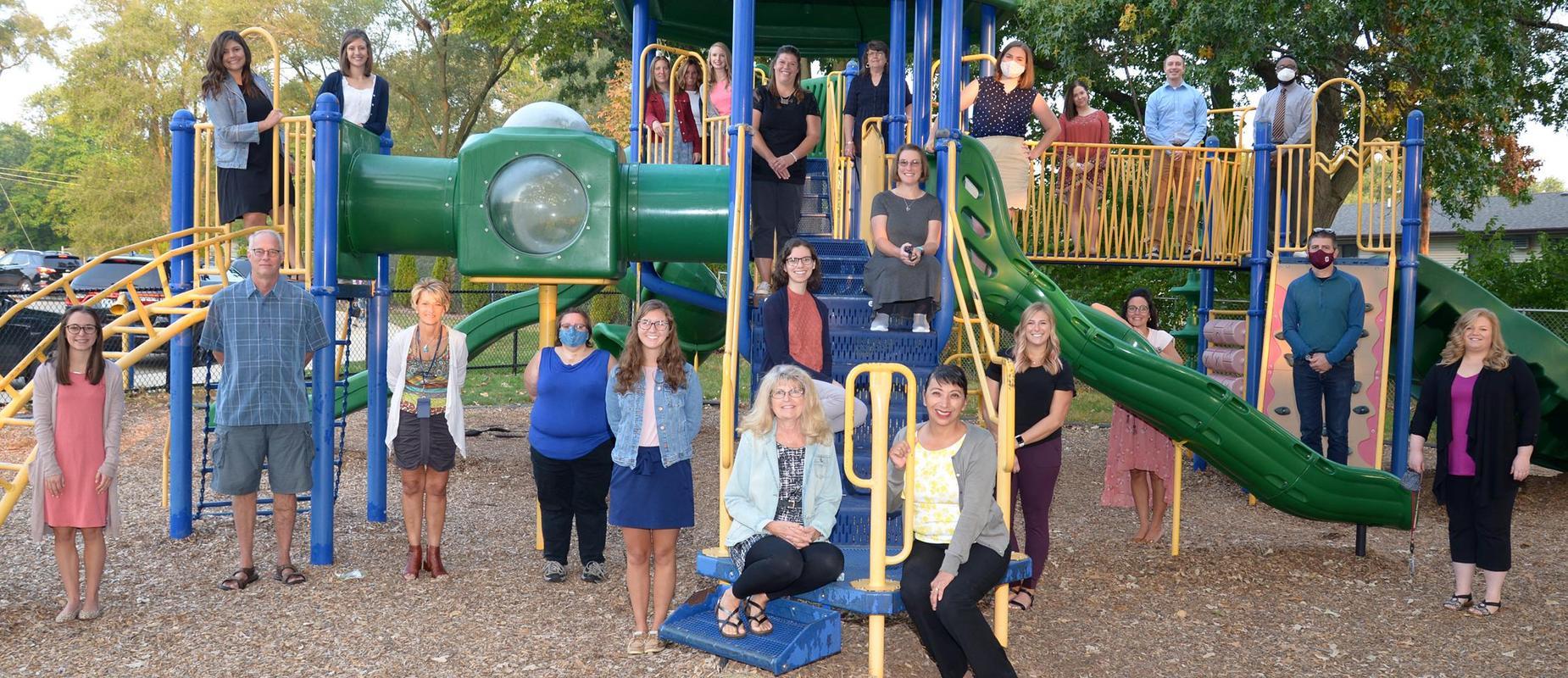 photo of staff standing on playground equipment 6 feet apart